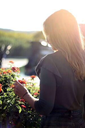 Women back shot holding flower with sunset light