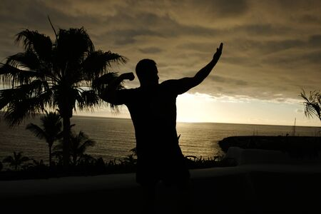 Fit man posing silhouette with sunset over the ocean