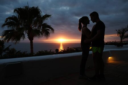 Silhouette of a hugging couple and palm tree with sunset over the sea Stock Photo