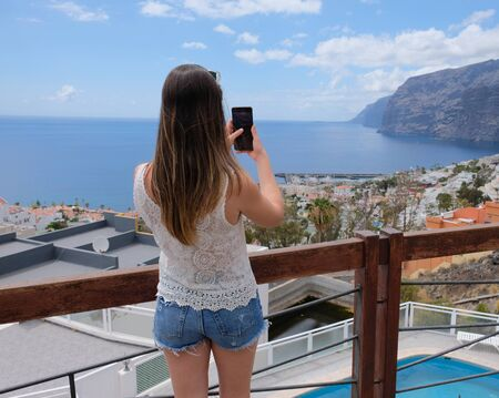 Girl taking photos of Los Gigantes from Tenerife island