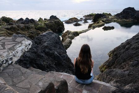 Girl sitting on volcanic rocks looking at natural pool and sea