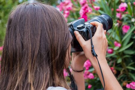 Girl taking pictures of flowers with DSLR camera Zdjęcie Seryjne
