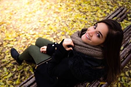 Beautiful woman sitting on a bench surrounded by yellow fall leaves top shot