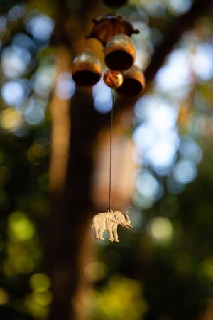 Close up of hanging bells with elephant charm with green leaves in the background Фото со стока