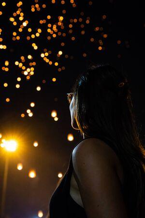 Beautiful woman looking at Loy Krathong paper lanterns as bokeh on background in Thailand