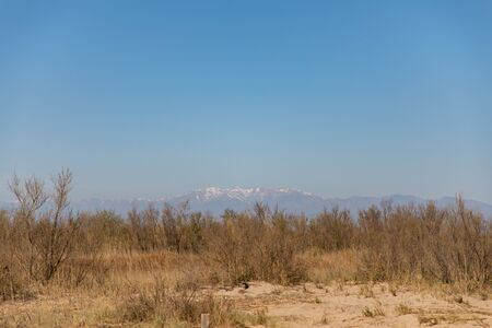 Landscape shot with far snowy mountain with clear sky and copy space