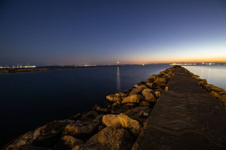 Late night sunset view of a calm sea from a breakwater on the side