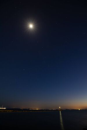 Long exposure night shot of the sky over the calm sea with town lights and the bright moon and stars Stock fotó