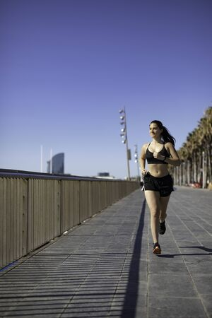 Beautiful woman in sport clothes running on the seafront in Barcelona (SPAIN) front shot in the morning Stock Photo