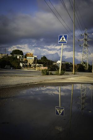 Crosswalk sign with pond reflection on a cloudy day with dark blue sky and copy space from Spain Banco de Imagens