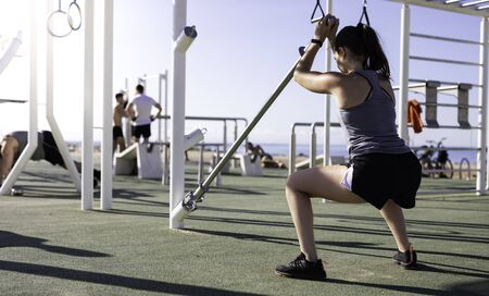 Beautiful woman doing squats with weight bar at outdoor training spot or street workout in Barcelona