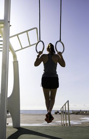 Beautiful woman hanging on gymnastics rings at outdoor training spot or street workout in Barcelona beach (SPAIN) 写真素材