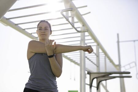 Beautiful woman stretching at outdoor training spot or street workout in Barcelona beach (SPAIN)