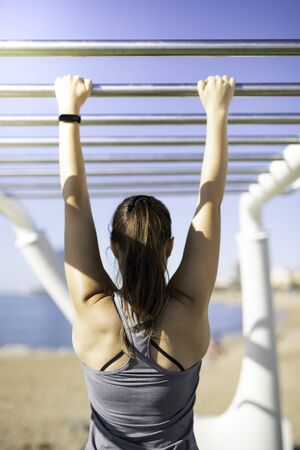 Beautiful woman hanging on bar at outdoor training spot or street workout in Barcelona beach (SPAIN) with copy space