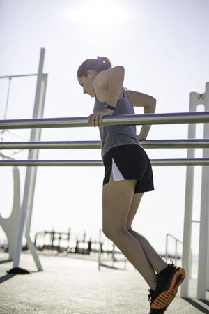 Beautiful woman doing dips on bar at outdoor training spot or street workout in Barcelona beach (SPAIN) with copy space 写真素材