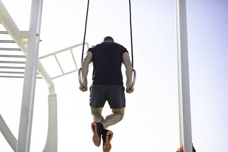 Handsome strong man hanging on gymnastics rings at outdoor training spot or street workout in Barcelona beach (SPAIN) 写真素材