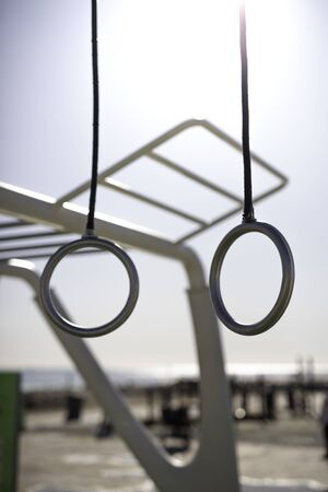 Gymnastics rings at outdoor training spot or street workout with blue clear sky on background in Barcelona beach (SPAIN)