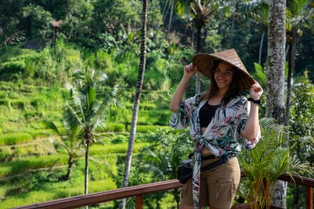 Beautiful woman with asian hat on rice terrace in Bali (Indonesia) with copy space Banco de Imagens