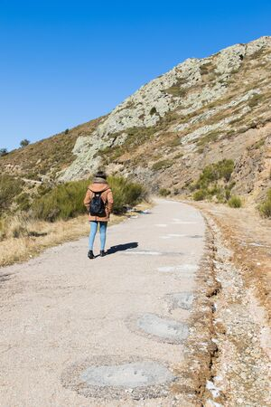 Beautiful woman hiking on mountain path during winter or autumn in Catalonia (Turo del Home - Spain) with copy space