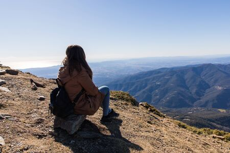 Beautiful woman sitting after hiking during winter or autumn in Catalonia (Turo del Home - Spain) with copy space Imagens