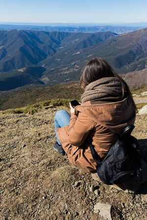 Beautiful woman sitting after hiking with the phone during winter or autumn in Catalonia (Turo del Home - Spain) with copy space Imagens