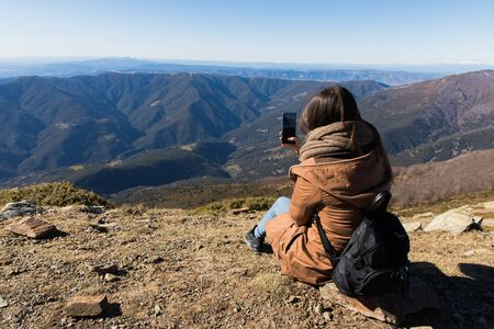 Beautiful woman sitting after hiking and taking photo with phone during winter or autumn in Catalonia (Turo del Home - Spain) with copy space Imagens