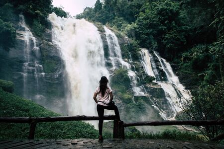 Beautiful woman at big waterfall after hiking in Chiang Mai (Thailand) with copy space Banco de Imagens