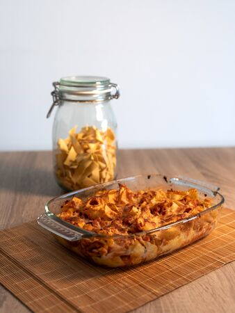 Close front view of a crystal tray of grated tagliatelle with vegan bolognese over a bamboo mat and a wooden table with copy space and white background