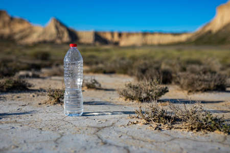 Unlabeled plastic water bottle on arid soil into desertic landscape with copy space