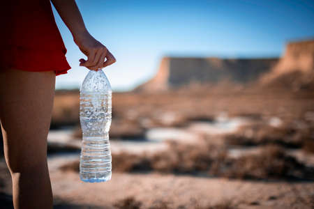 Unrecognizable woman holding unlabeled plastic water bottle on arid soil into desertic landscape with copy space