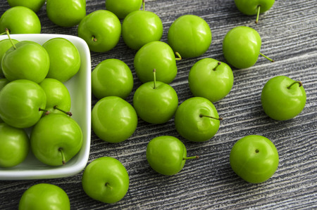 Green sour plums in the plate, plum pictures on the white ground, Stock Photo
