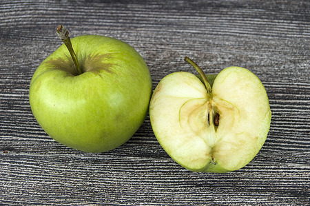 A whole and half green apple