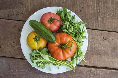 Pinturas orgánicas naturales de los tomates y del pepino, verduras del desayuno en la flor de madera Foto de archivo - 85627303