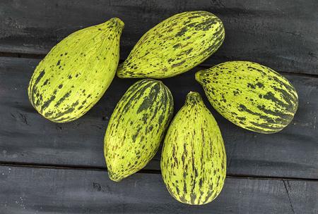 Volle unreife kleine Melonen, rohe Melonenbilder, schneiden eine kleine Melone mit einem Messer, essen eine unreife Melone, unreife kleine Melonen, Standard-Bild - 86693875