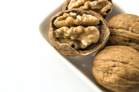 standing on the wooden plate on a white background dry walnut,