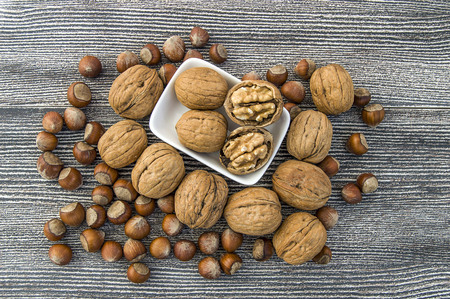 walnuts in the plate and hazelnuts around Stock Photo