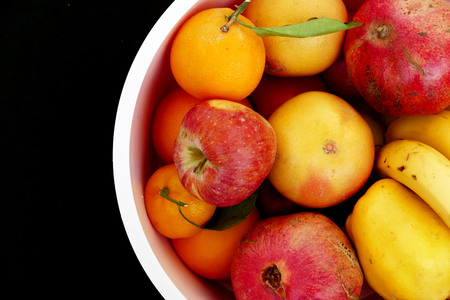winter fruit in a bowl on a black background