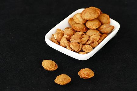 apricot kernels on black background Banco de Imagens