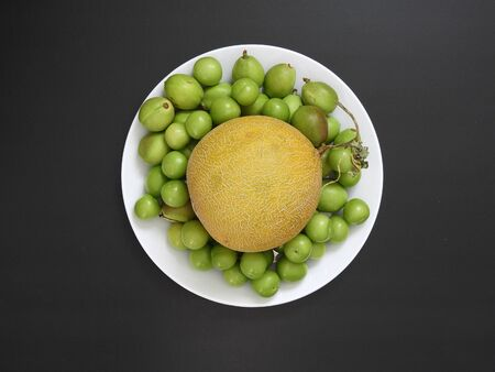 a whole melon, green sour plum and nectarine fruits in a plate on a black ground,