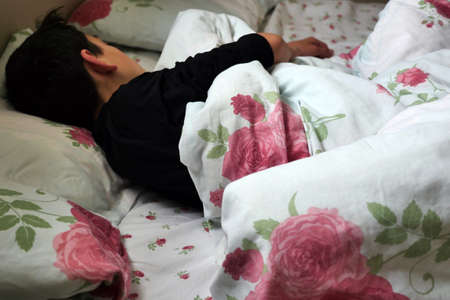 a teenager sleeping in bed, spending time sleeping during the day, daytime sleep, Stock fotó
