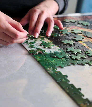 A teenager assembling puzzle pieces, spending time at home, home hobbies,