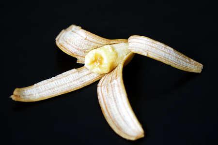 banana peel, peeled half a banana on a black background, Stock fotó