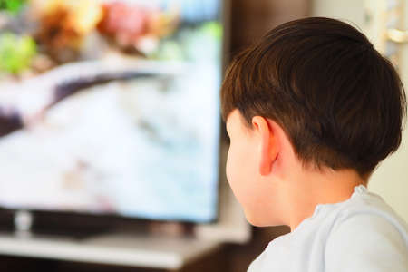 a child watching television, television and cartoon addiction, a child and watching television,