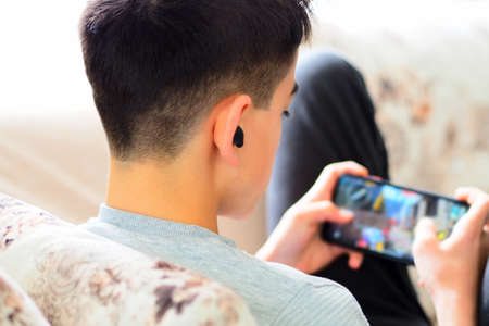 a teenager playing a game with a cell phone, Phone addiction in the z generation
