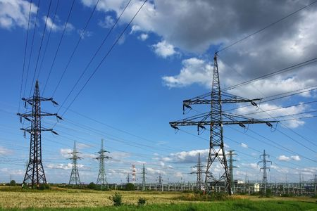 electricity pylons in the green field photo