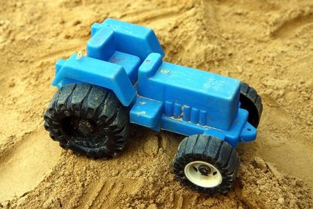 small blue children plastic tractor toy in the sand photo