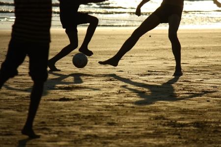 football silhouette: partita di calcio sulla spiaggia contro il sole