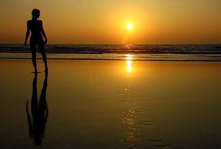 若い女の子、日没時に、ビーチでのヨガの練習