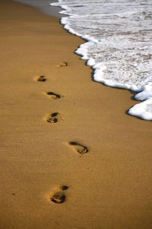 footstep on the sandy indian beach with foam of water