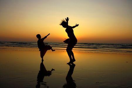 mere cuisine: silhouette de la m�re et son fils sur la plage pendant le coucher du soleil  Banque d'images